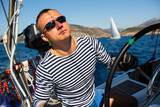 Skipper at the helm controls of a sailing yacht. - 224982247