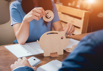 Business woman holds a coin near wooden piggy. Money box. Collecting money with earning bank.