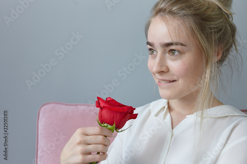 Leinwandbild Motiv Portrait of romantic gorgeous young female with gathered fair hair having playful dreamy expression, biting lips, posing indoors with beautiful red rose from mysterious admirer. Valentine's Day