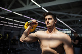 Unrecognizable bodybuilder doing kettlebells swing working out at gym