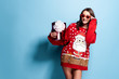 Pretty brunette woman in sunglasses and red oversize pullover with Santa design holding gift box while standing on blue background in studio. Isolate