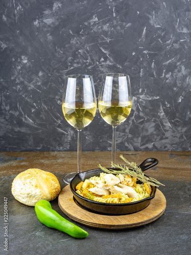 wine and Italian pasta with chicken in a black frying pan - 225049447