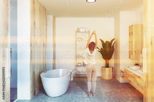Leinwanddruck Bild White bathroom interior, sink and tub, woman