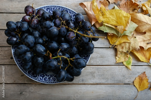 Bowl of grapes on a rustic wooden table decorated with autumn leaves