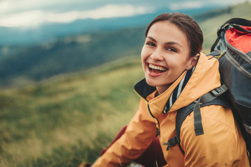 Delighted young woman resting on the slopes of the mountain while feeling happy