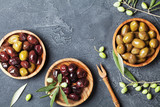 Natural olives in bowls with olive branch on black stone table top view. - 225125056