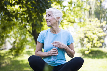 Senior woman rests and drinks water after workout