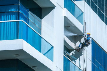 Worker wearing safety harness washes glass facade at height on modern high rise building. Professional rope access