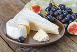 Cheese with fig and grapes on wooden table.