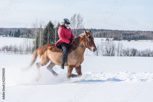 Woman on a galloping horse during winter.