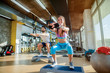 Happy strong couple working out in a gym. Using stepper for their workout and looking at the camera.