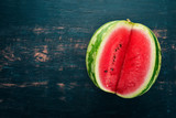 Fresh watermelon Fruits. Melon. On a black wooden background. Free space for text. Top view.