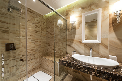 Luxury decorated bathroom, glass shower, sink and mirror