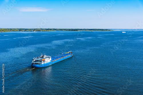 Fototapeta Cargo ship sailing on the sea or river