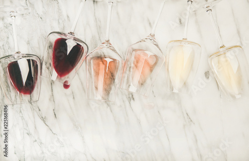 Leinwandbild Motiv Flat-lay of red, rose and white wine in glasses and corkscrews over grey marble background, top view, copy space. Bojole nouveau, wine bar, winery, wine degustation concept