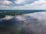 Aerial view of river Volga and cargo ship sailing along. Green riversides and cloudy sky. Summer photo from drone, Russia - 225168856