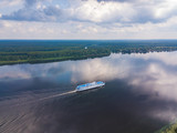 Aerial view of river Volga and cruise ship sailing along. Green riversides and cloudy sky. Summer photo from drone, Russia - 225168865