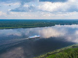 Aerial view of river Volga and cruise ship sailing along. Green riversides and cloudy sky. Summer photo from drone, Russia - 225168870