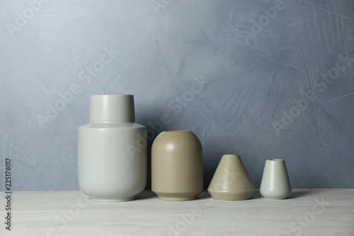 Leinwandbild Motiv Beautiful ceramic vases on table against color wall. Space for text