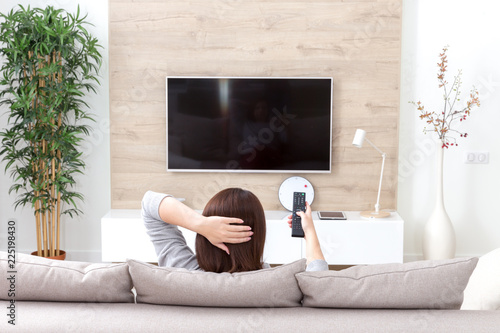 Young woman watching TV in the room - 225198430