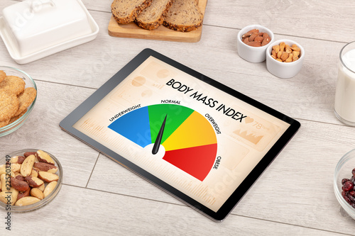 Leinwandbild Motiv Healthy food with tablet on a wooden background with words Body Mass Index. Health concept.