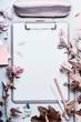 Modern desktop background with gray clipboard, blank paper sheet , office accessories and flowers. Top view, flat lay.  Instagram style