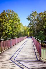 Bunte Holzbrücke im Herbst, Bäume und blauer Himmel