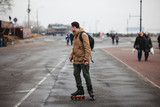 A middle aged man learns to skate on a cloudy cold and wet weather. First time skating concept. - 225231255