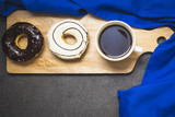 Chocolate and withe cream donuts and cup of coffee on a wooden tray