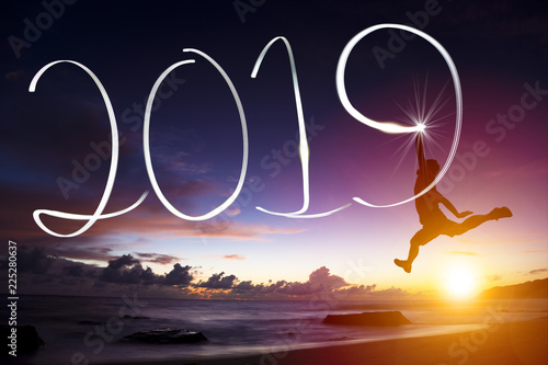 Leinwandbild Motiv happy new year 2019. man jumping and drawing on beach