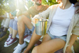 Steel mug with hot tea in hand of young woman during talk to her boyfriend on backpack trip - 225285008