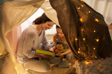 family, hygge and people concept - happy mother and little daughter reading book in kids tent at night at home - 225285839