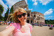 Tourist woman posing in front of Colosseum in Rome