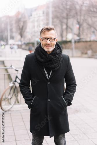 geschäftsmann im mantel steht draußen auf der straße