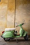 Green scooter parked under an archway in a street in Siena, Tuscany
