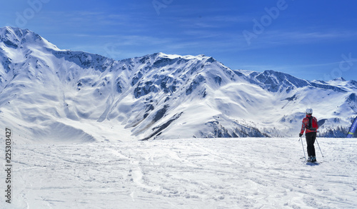 skier on a slope in alpine snowy mountain under blue sky