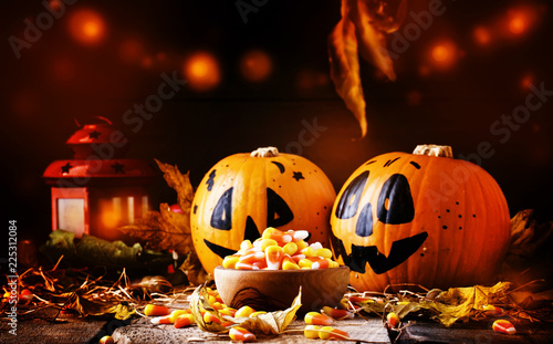 Leinwanddruck Bild Halloween festive composition with sweet corn in bowl and smiling pumpkins guards, lantern, straw and fallen leaves on dark wooden background, rustic style, selective focus