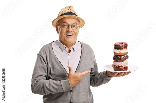 Smiling senior man holding a plate of donuts and pointing