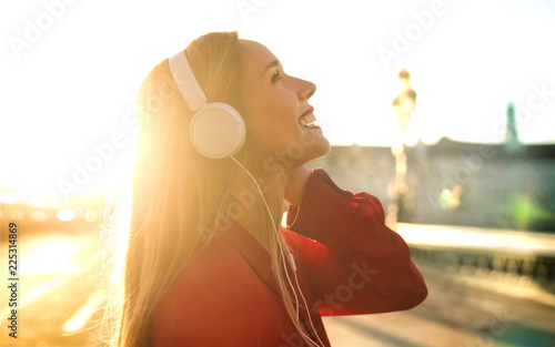 Beautiful girl listening music with headphones while walking in the street - 225314869