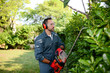 Leinwandbild Motiv handsome young man gardener trimming hedgerow in a garden park outdoor