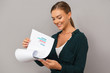 Woman posing isolated over grey wall background holding clipboard with graphics.