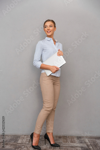 Happy business young woman posing isolated over grey wall background holding laptop computer.