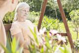 Weak elderly woman during treatment in the hospital's garden during summer - 225333209