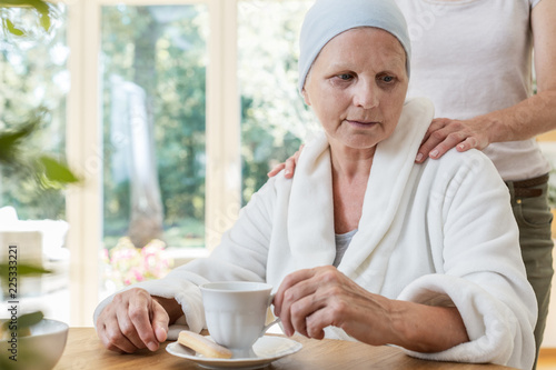 Foto Murales Family member supporting sick elderly woman with cancer while drinking tea