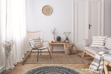 Armchair and sofa with patterned pillows in white flat interior with plants and round rug. Real photo