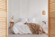 Leinwanddruck Bild - Wooden door and lamp in white bedroom interior with blanket on bed and flowers on table. Real photo