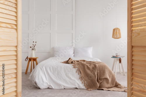 Leinwanddruck Bild Wooden door and lamp in white bedroom interior with blanket on bed and flowers on table. Real photo