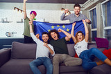 A group of friends with a European flag at a party. Friends celebrate the day of Europe. - 225334481