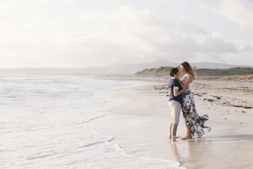 Young couple in love hug each other on the deserted beach on a summer evening © loreanto
