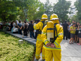 Select focus of back Firefighters in yellow suit with an oxygen tank in the back. Firefighters are teaching office workers to escape from high-rise buildings (Fire Drill).